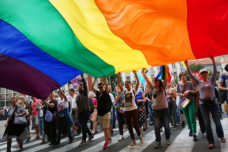 lgbtq pride march - activists holding large rainbow flag over head